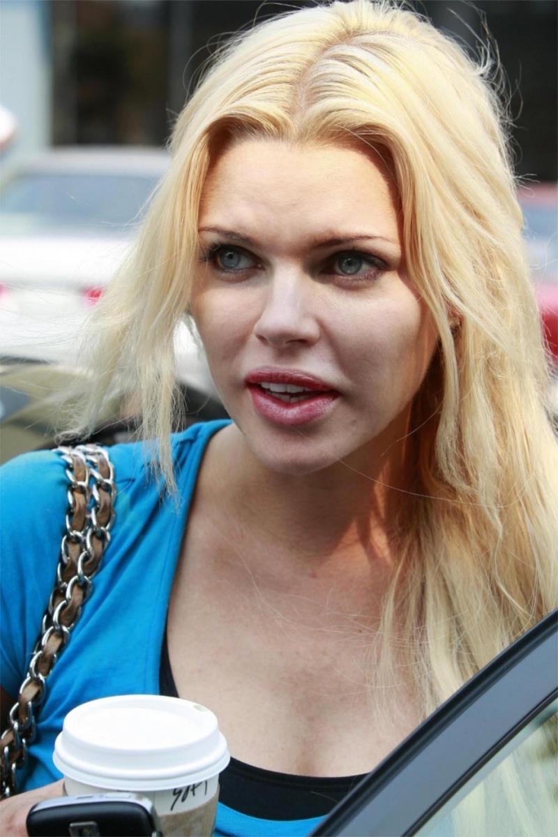 Sophie Monk siyah taytı ve mavi bluzuyla sokakta