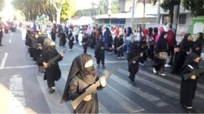 Anaokulu öğrencileri peçeli ve 'silahlı' şekilde yürütüldü
