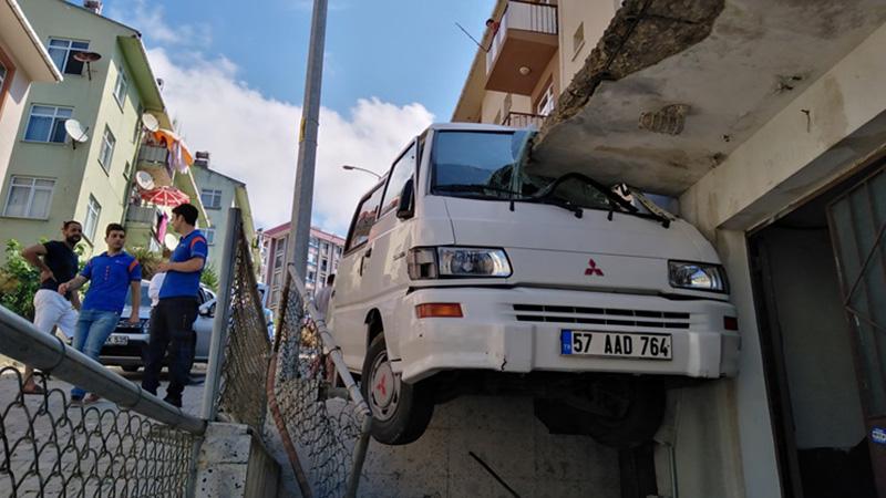 Kontrolden çıkan minibüs, zemin katın balkonu ile yol arasına sıkıştı