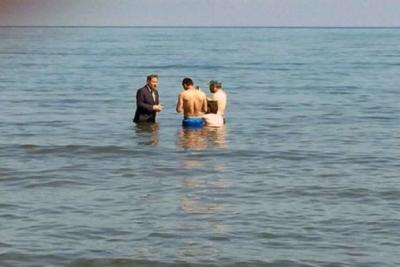 Takım elbiseyle denize girip yüzenlerden oy istedi